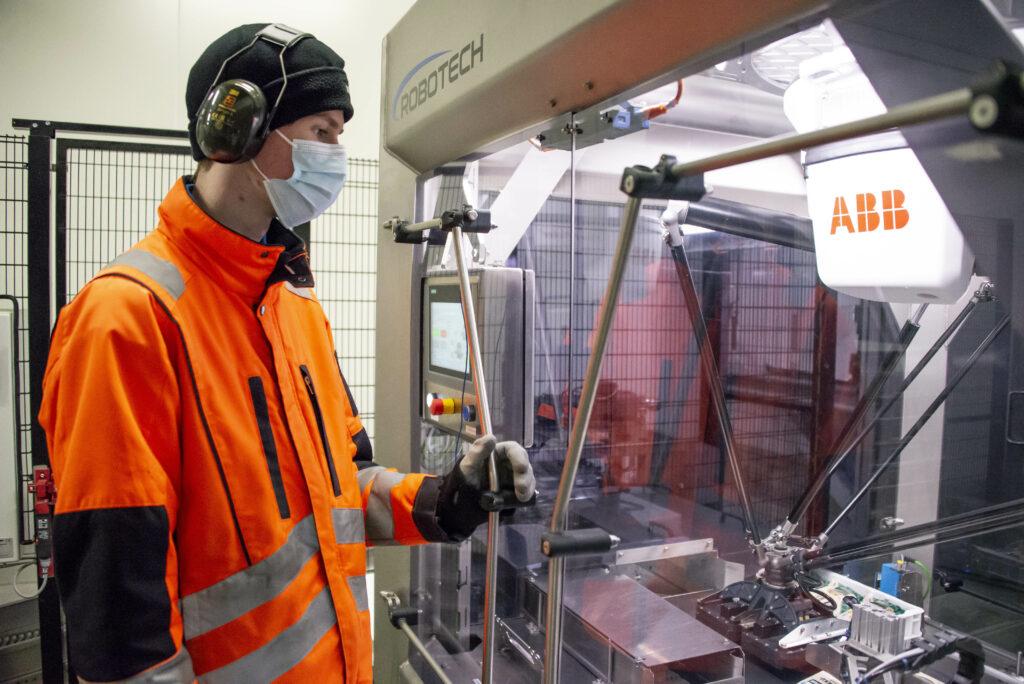 Kiusaustuotteita pakkaavan robotin ohjaaminen on yksi Alin työtehtävistä. Enimmäkseen se tarkoittaa koneen valvomista, mutta välillä myös häiriöiden korjaamista.